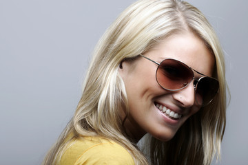 Attractive and cheerful female model in sunglasses