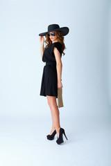 schöne frau mit schwarzem kleid, hut und sonnenbrille