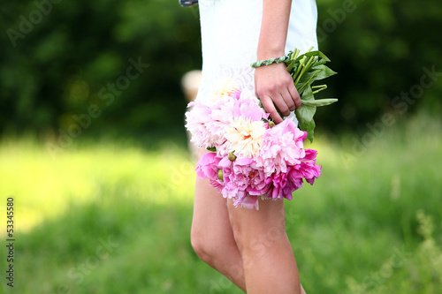 Peonies bouquet in woman's hand outdoors