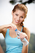 Young beautiful woman drinking water after fitness exercise outd