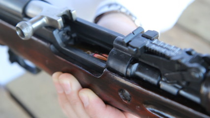 Loading bullets into a Russian 1954 Tula SKS carbine rifle.