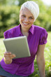 Smiling woman with tablet pc is sitting on the grass while smili