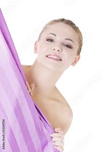 Beautiful woman covering her body with shower curtain