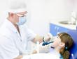 dentist using dental filling gun on kid