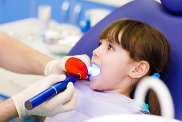 little girl with open mouth receiving dental filling drying
