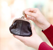 Hands holding coin and retro styled money pouch in mall