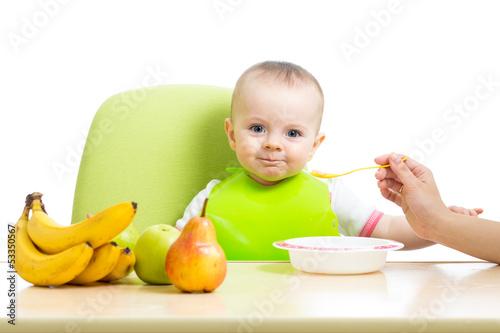 mother spoon feeding baby girl