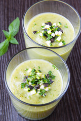Vegetable cream soup with avocado, herbs, zucchini and black oli