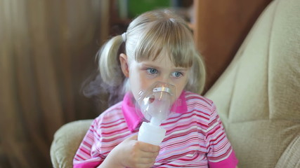 Girl makes inhalation with nebuliser