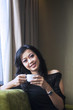Asian female drink coffee in apartment