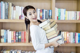 Attractive female bring stack of books in library