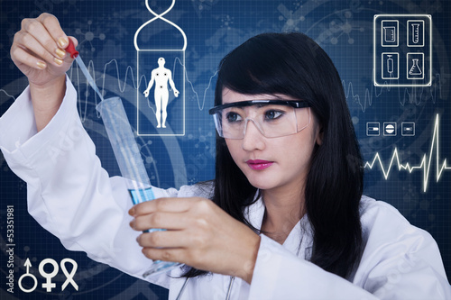 Attractive female scientist using pipette on blue background