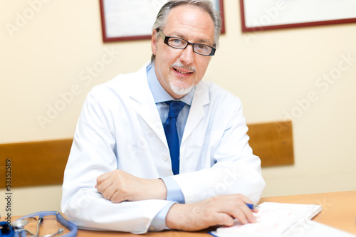 Mature doctor at his desk in his studio