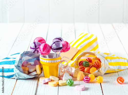 Assortment of candies in bags and cup over a table