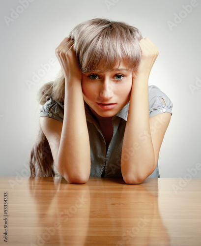 A young tired woman sitting at the desk