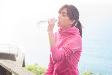 Young woman drinking from a plastic bottle of water