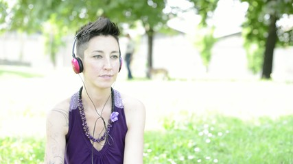 beautiful hipster short hair woman listening music in the park