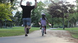 Proud Father Encourages Daughter Riding Her Bike