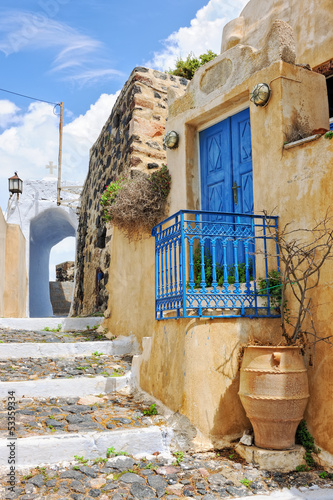 House with blue door and railing in a lane in Pyrgos