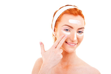 Skin care woman putting face cream touching under eyes.