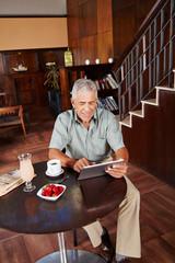 Senior nutzt Tablet PC im Hotel