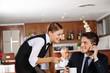 Kellnerin gießt Mann Kaffee ein