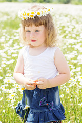 Blond baby girl in wreath in field of camomiles