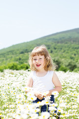 Blond baby girl in field of camomiles