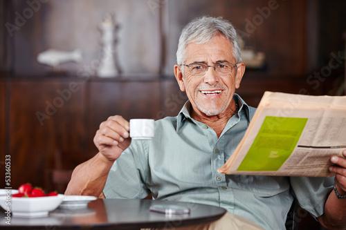 canvas print picture Senior mit Kaffee und Zeitung im Café