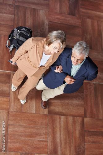 Zwei Senioren gehen mit Koffer