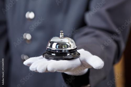 Hand mit Hotelglocke