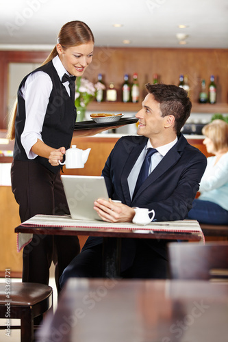 Kellnerin bedient Geschäftsmann im Café