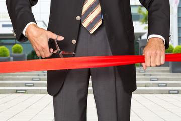 Einweihung - Geschäftsmann durchschneidet rotes Band
