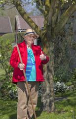 fröhliche Rentnerin mit Daumen hoch bei der Gartenarbeit
