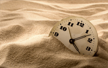 Face of clock in sand