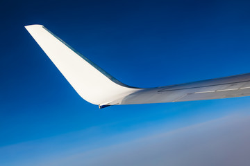 Airplane wing.  Wing of an airplane flying above the clouds.