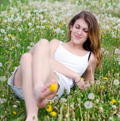 Young woman enjoys spring between dandelions