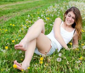 Junge Frau entspannt auf Wiese mit Löwenzahnblüten