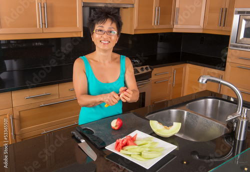 Asian Woman in Kitchen Chopping Fruit
