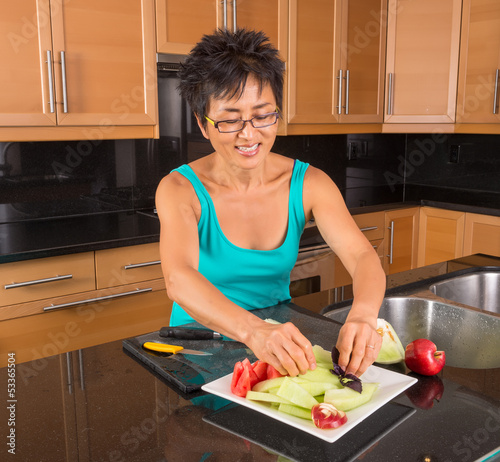 Asian Woman in Kitchen Prepares Fruit Plate