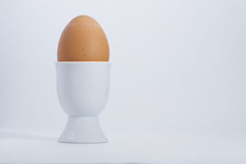Boiled egg in white egg cup