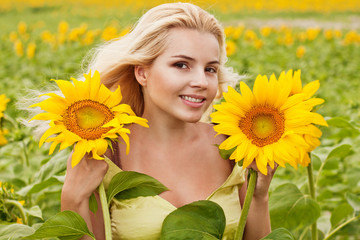 beautiful long-haired young woman in the field with sunflowers