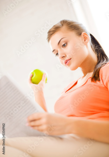 woman with green apple reading newspaper at home