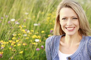 Glückliche blonde Frau in Blumenwiese