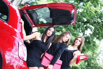 drei junge Frauen im Kofferaum