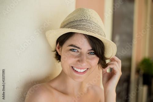 lächelnde junge frau mit strohhut in der stadt