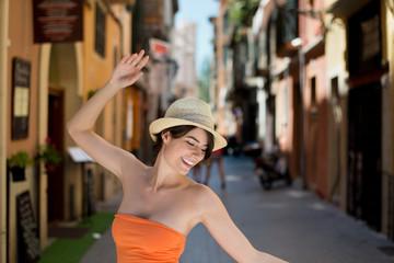 lachende junge frau tanzt auf der straße