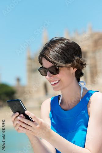 lächelnde touristin schaut auf ihr handy