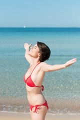 frau im bikini genießt die sonne am meer
