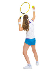 Female tennis player serving ball. rear view